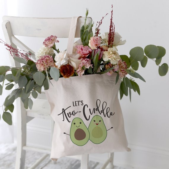 tote bag filled with flowers that says lets avo-cuddle with avocados on it