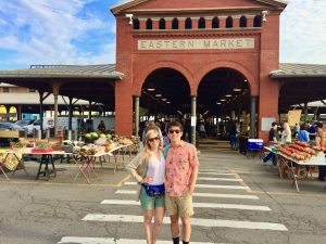 chelsea and chris standing in front of entrance of eastern market