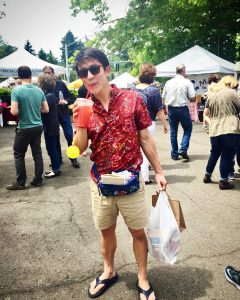 chris drinking juice holding bags at milwaukie market