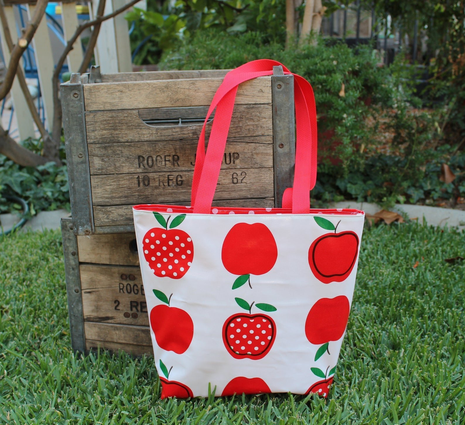 white tote with red apples on it and red handles