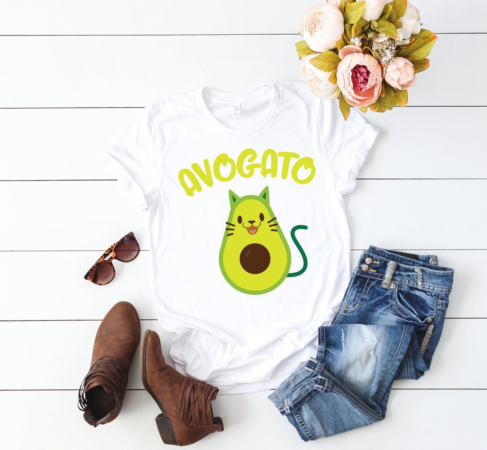 white t shirt with picture of avocado with cat face and tail that says avocato in green