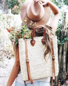 straw backpack on woman with hate on