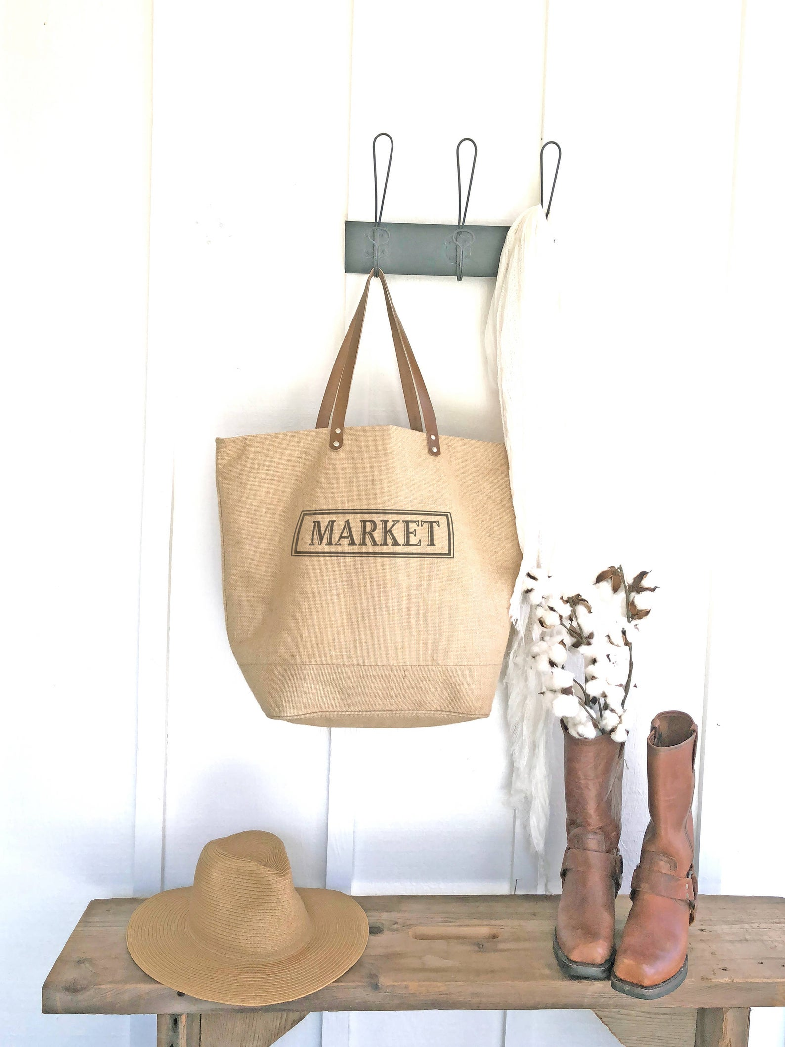 burlap tote that says market hanging on wall hook beside boots and hat