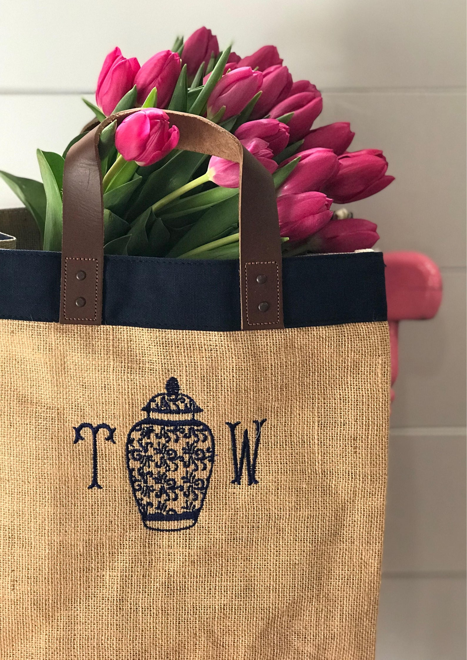 brown tote with monogram and pink flowers inside