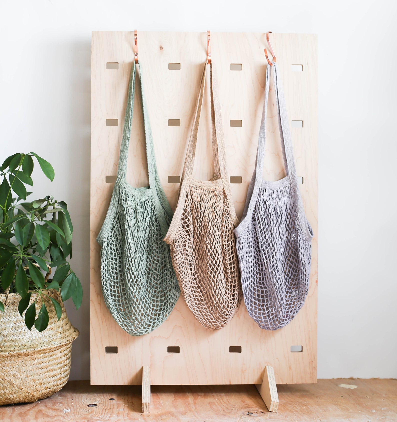 three net bags hanging on hooks in brown, green, and gray
