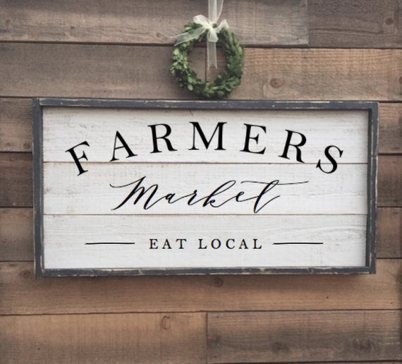 white sign in wooden frame that says farmers market eat local