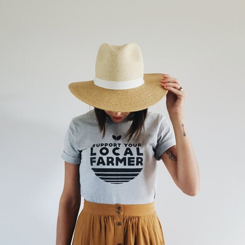 woman with hat on in shirt that says support your local farmer