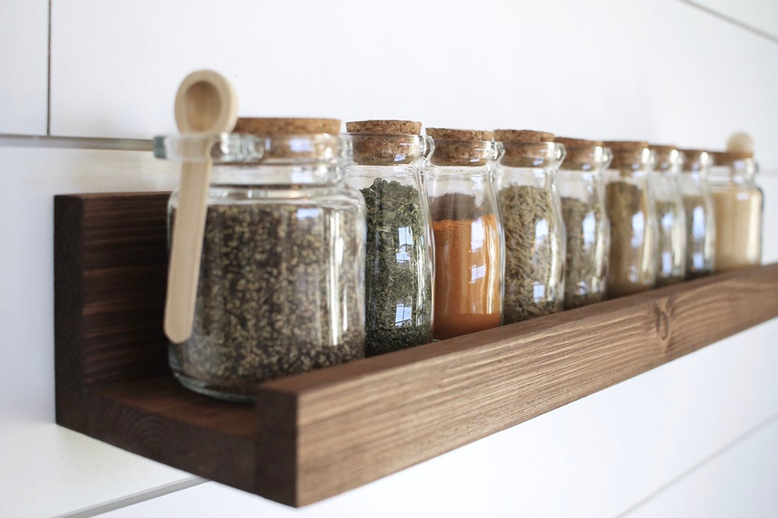 wooden shelf with bottles of spices on it