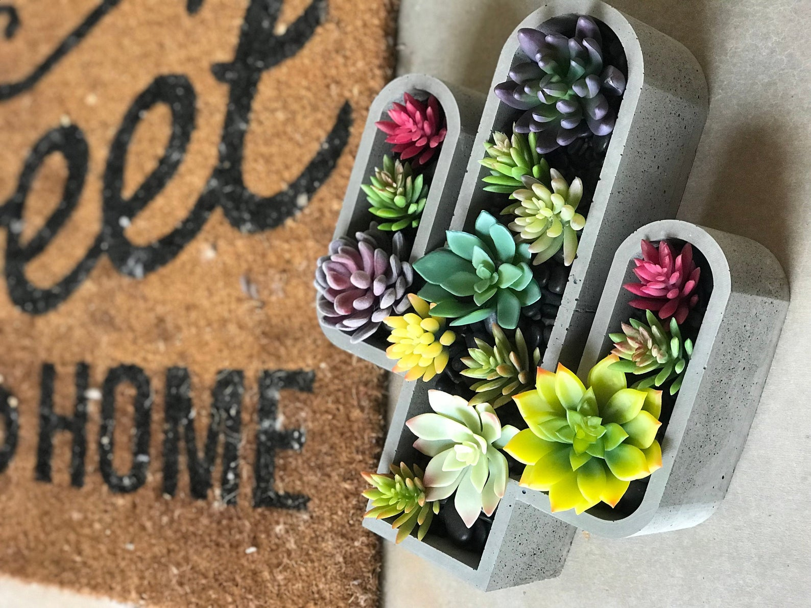 concrete planter shaped like cactus filled with succulents