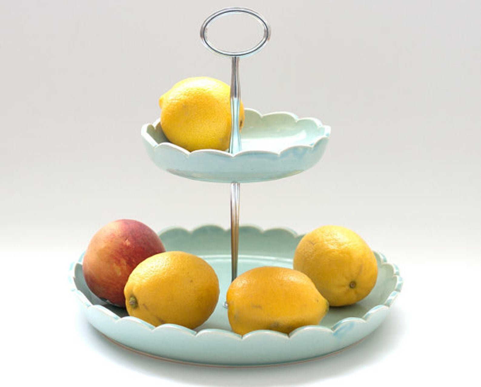 blue two tiered fruit basket with lemons and apple in it