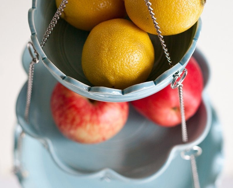 blue hanging basket with lemons and apples in it