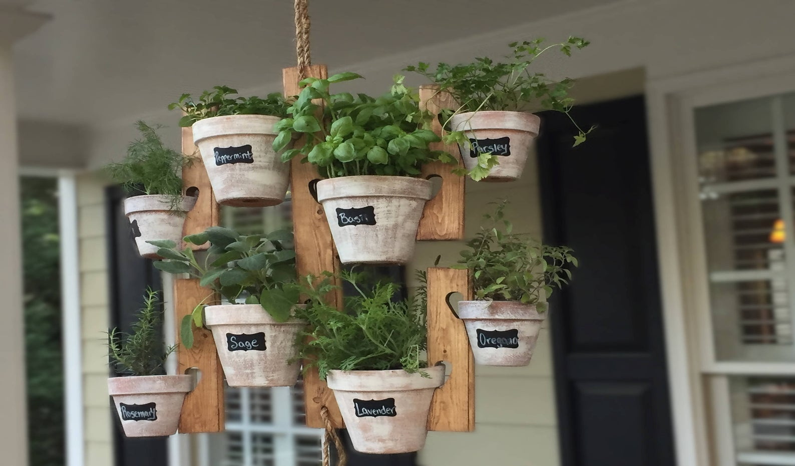 eight hanging pots labeled as herbs on wood holders