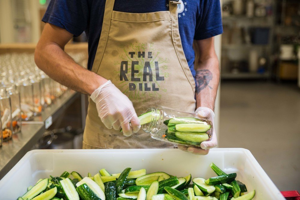 real dill worker putting pickles in jars