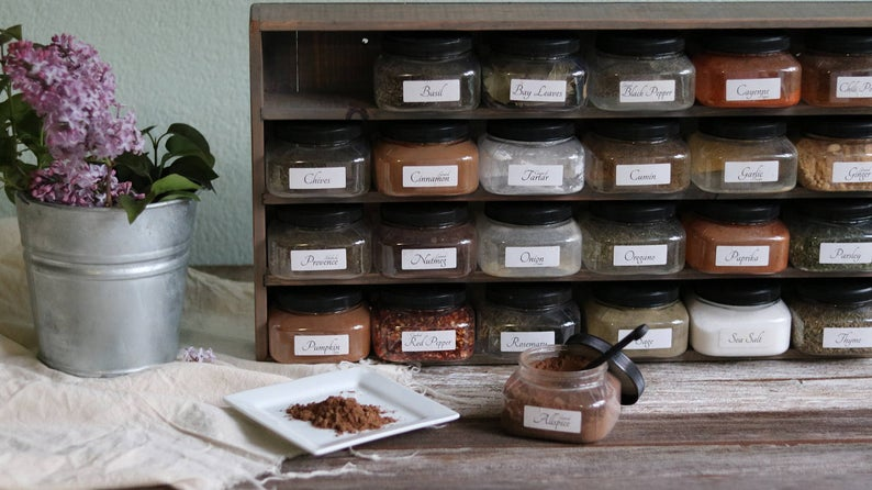 wooden spice shelf with spice bottles labeled inside