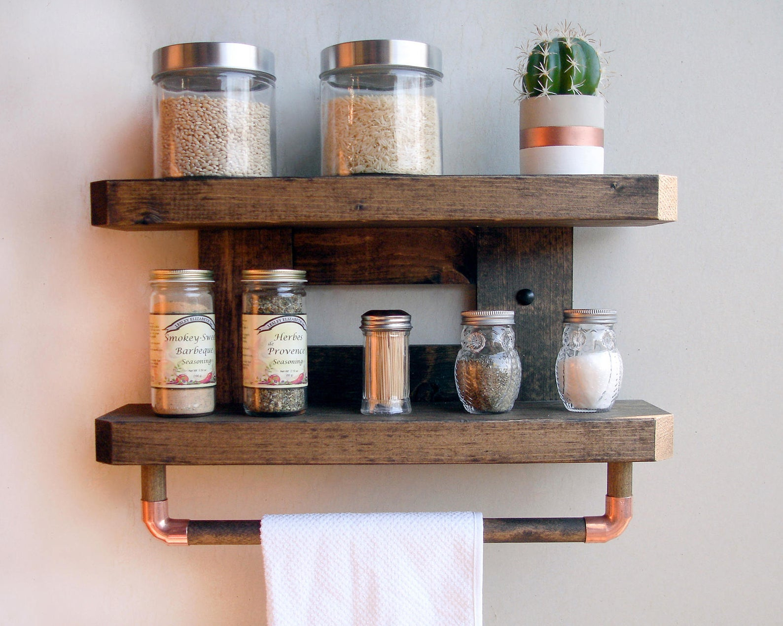 wooden wall rack with spices on it and tea towel hanging from rack