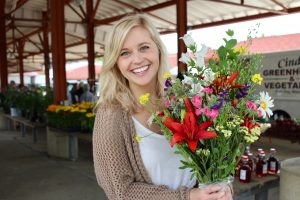chelsea holding flowers at farmers market