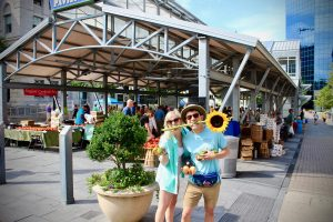chris and chelsea in front of lexington farmers market holding sunflower