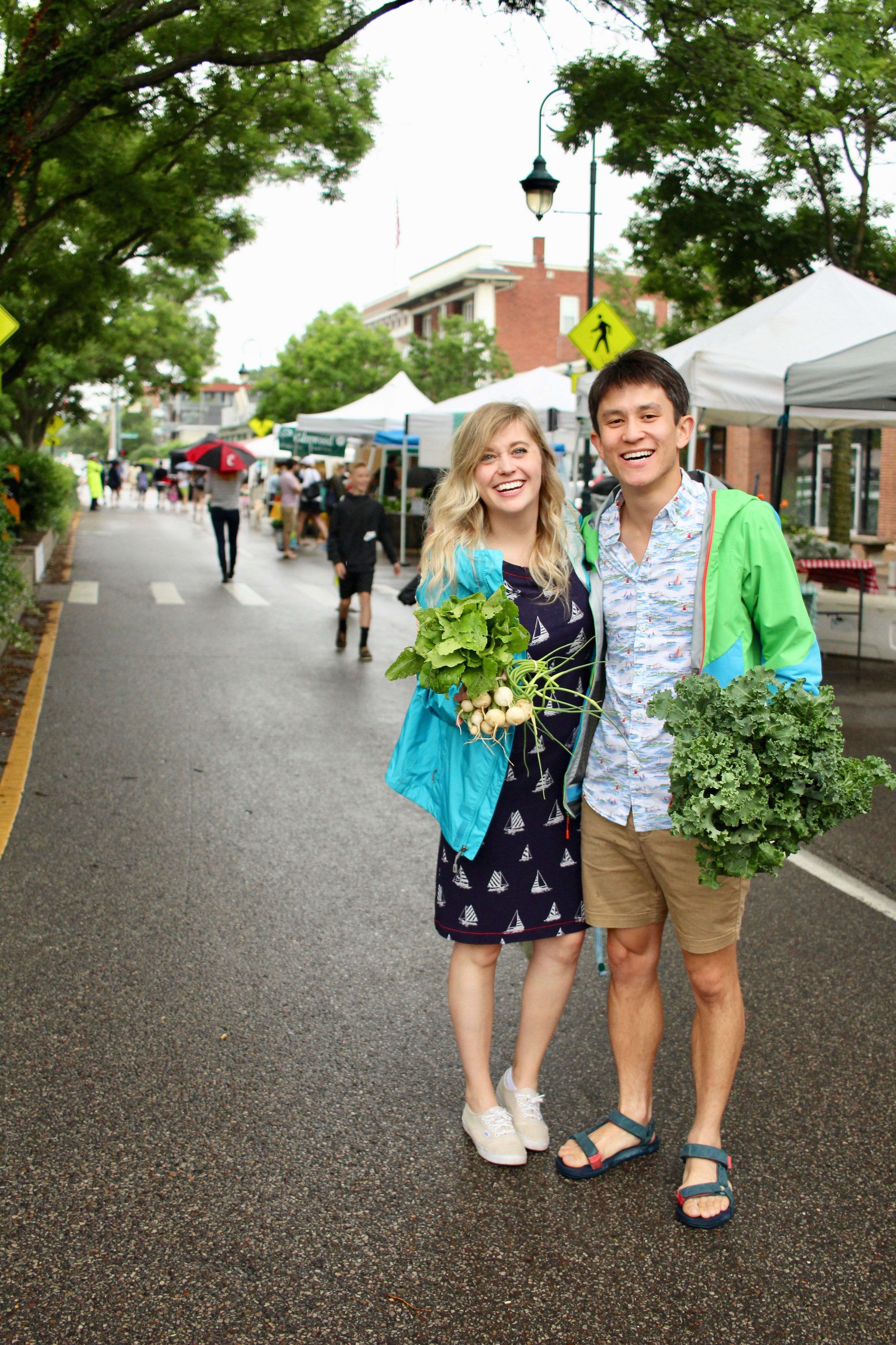 Chris and chelsea holding veggies at hyde park farmers market
