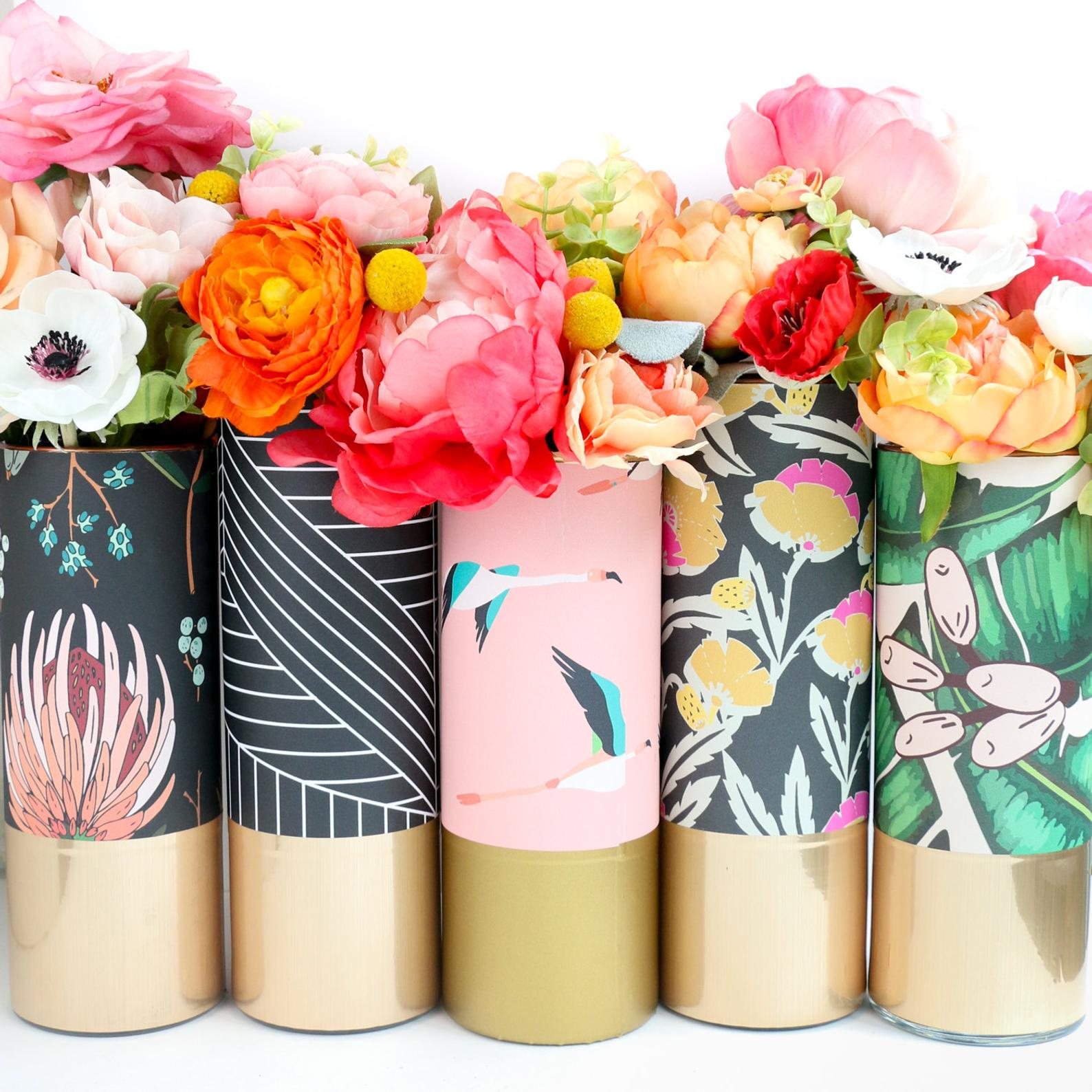 five vases with different patterns filled with flowers