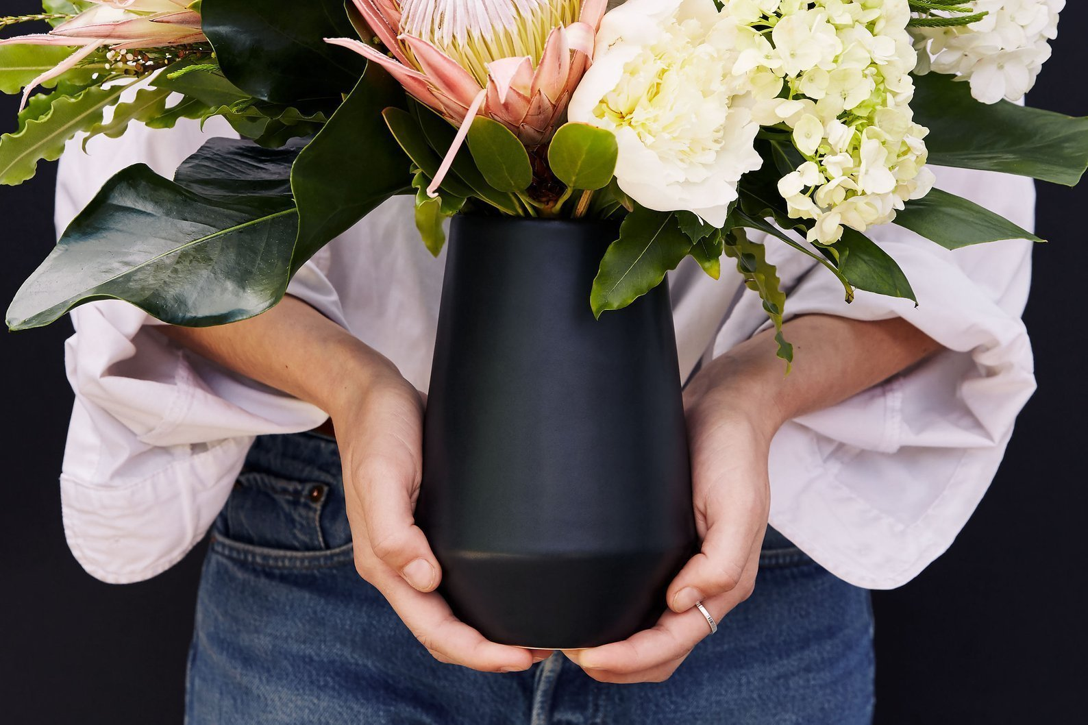 Black vase with white flowers