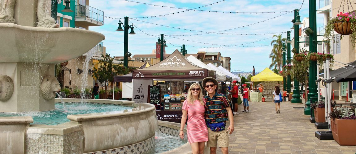 Chelsea and Chris standing by fountain at Little Italy Mercato