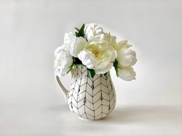 white chevron flower vase filled with white flowers