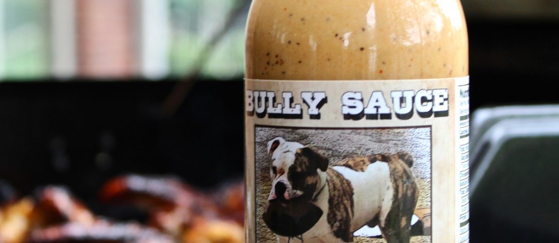 bully white bbq sauce bottle in front of wings on grill