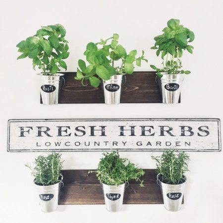 two wood shelves with 3 herb pots on each with chalked herb names