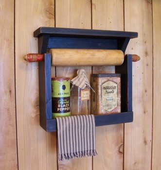blue wall spice rack with spices in it and rolling pin at the top