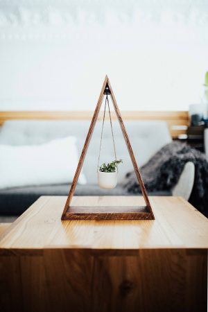 triangle wood planter with small pot hanging in middle